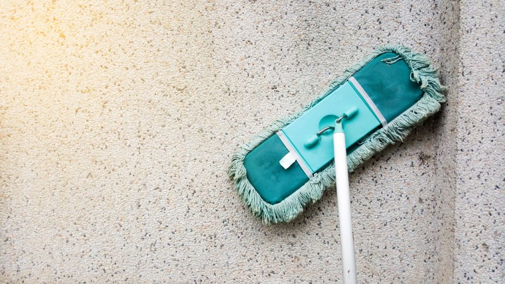 A mop is being wiped on a floor