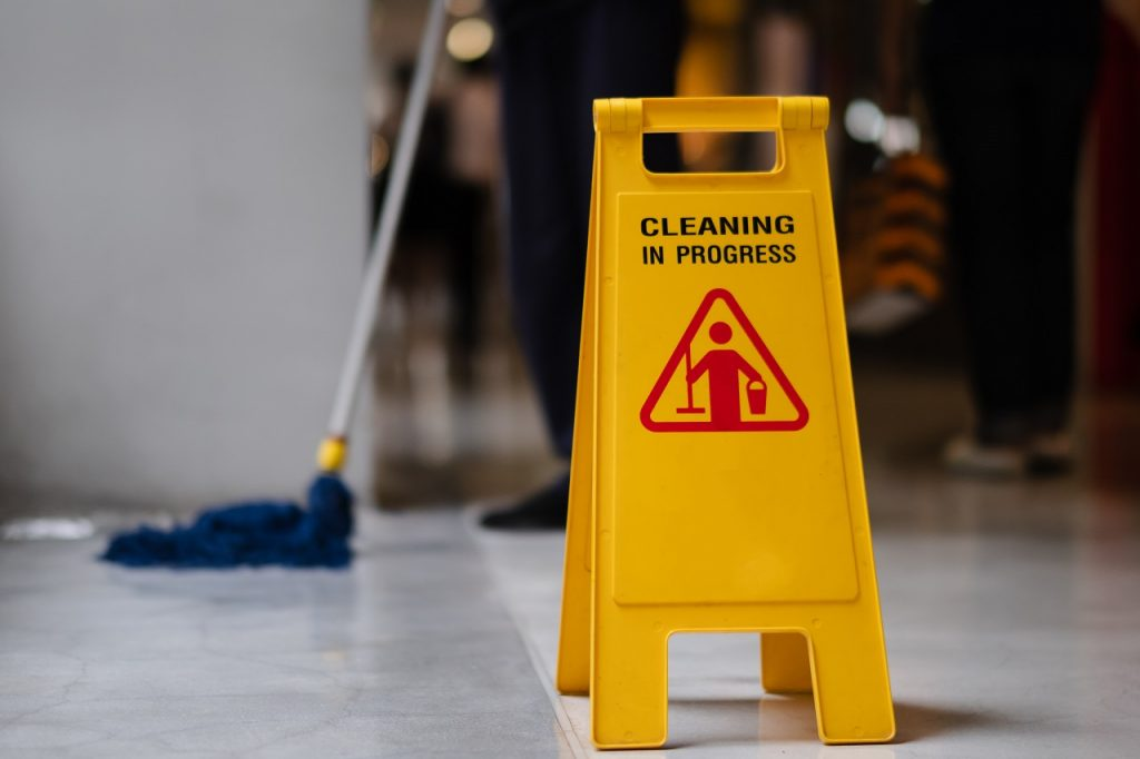 A yellow caution sign warning people that the floor is being cleaned