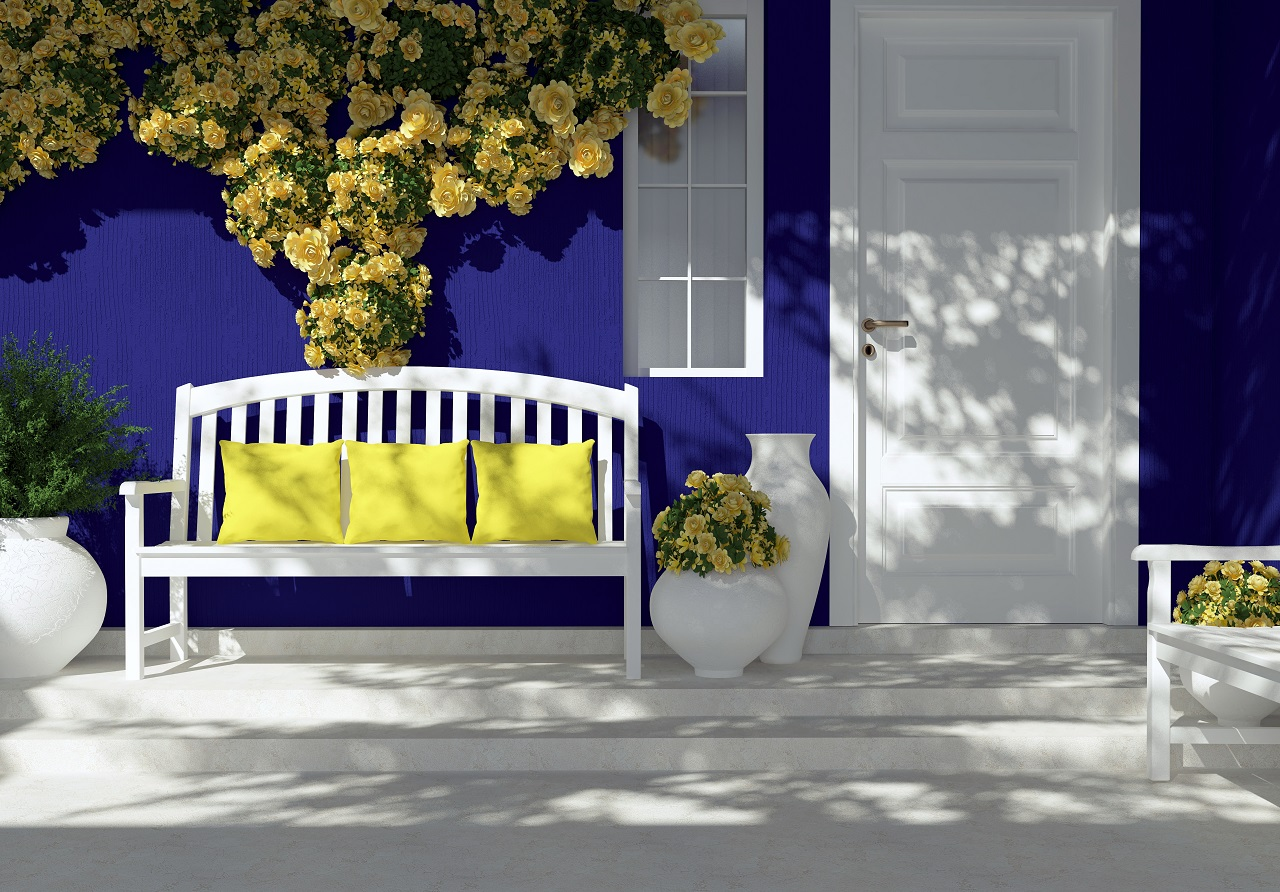 The patio of a house with blue walls and a white outdoor chair
