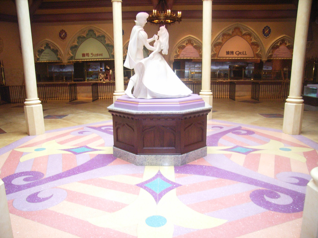 Wide shot of decorative flooring topped by a statue of a prince and princess