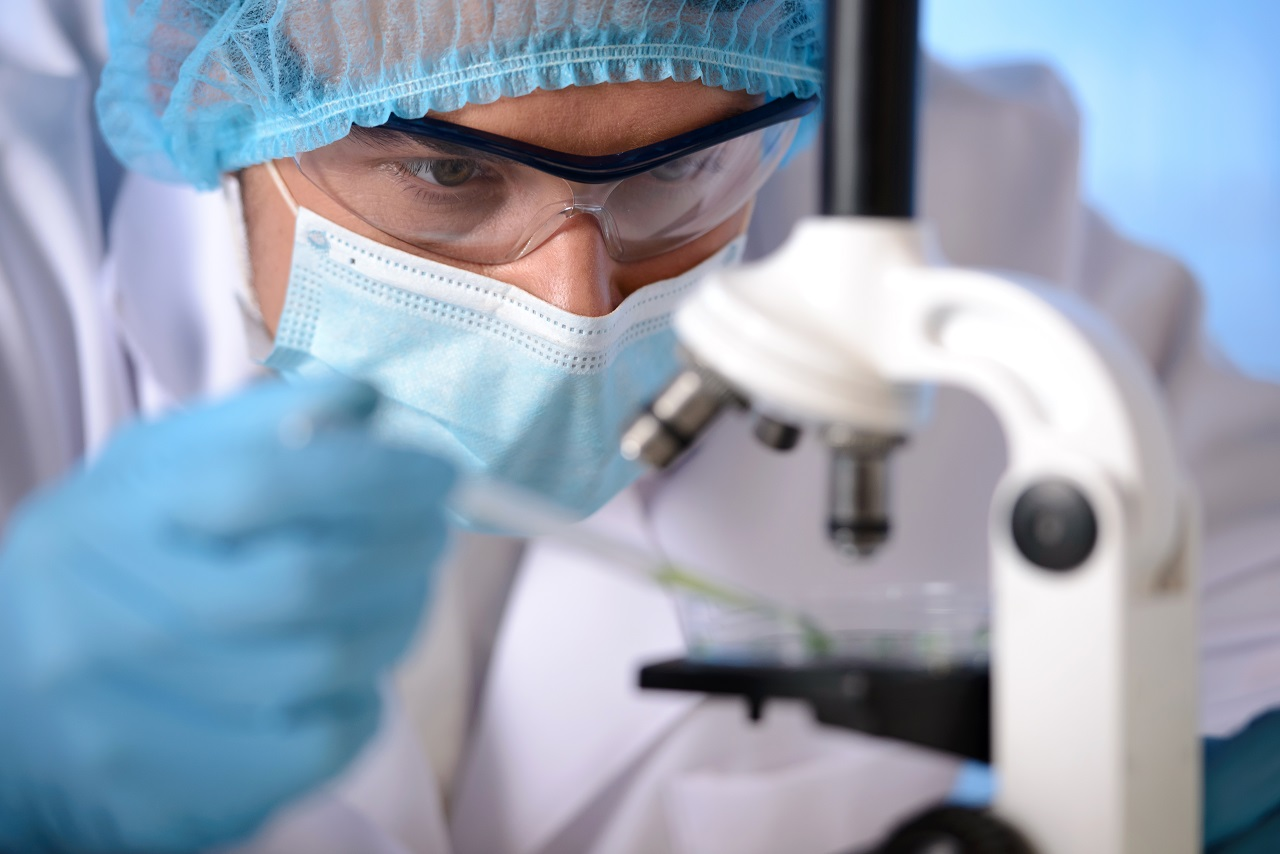 A scientist in a protective mask, glasses, and hair cap dropping a substance to examine