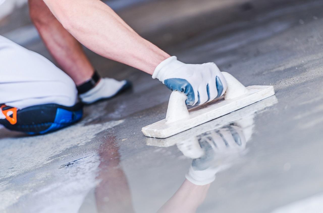 A construction worker flattening a concrete surface