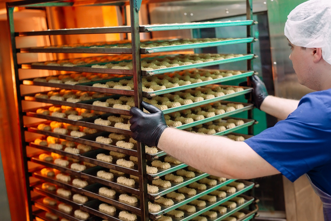 A worker pushing pastries in a factory