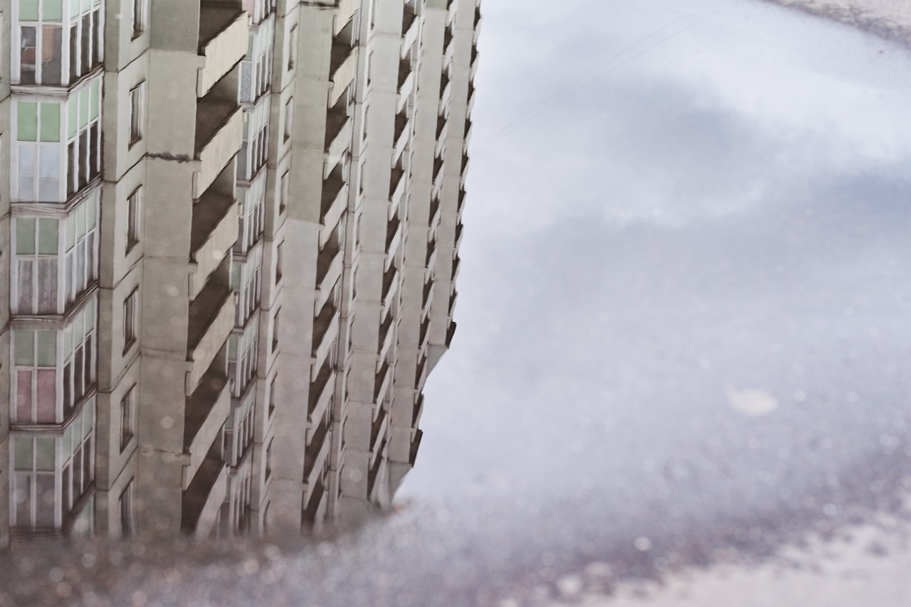 The reflection of a building on a puddle on a waterproof floor
