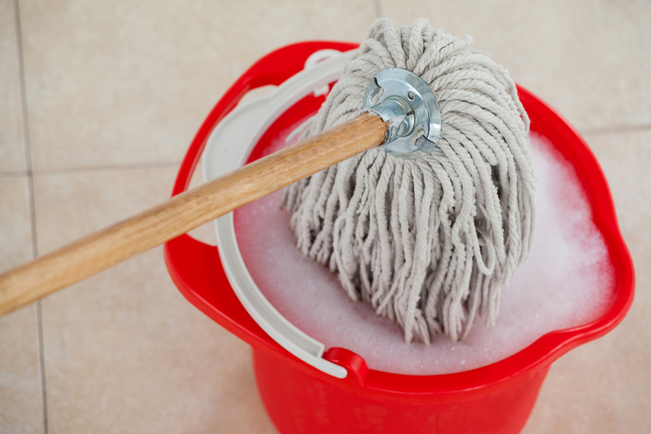 A bucket and mop to clean ceramic flooring