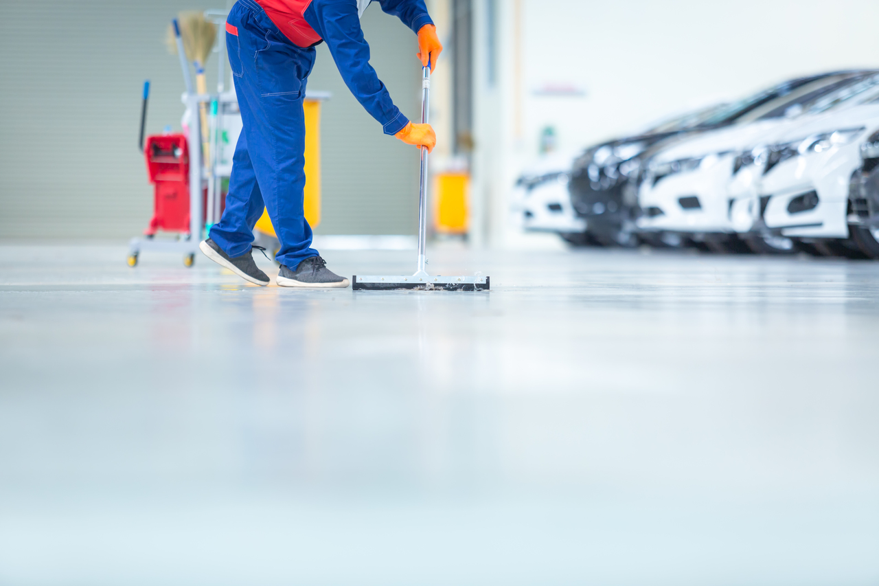 A worker cleaning the factory floor