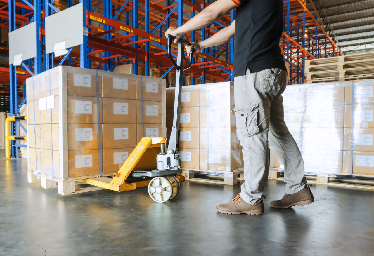 A man pulling cargo in a warehouse