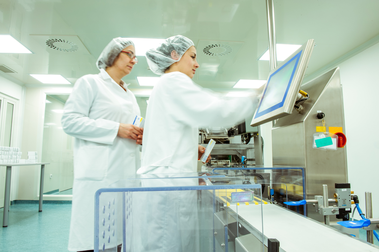 Two workers in a pharmaceutical facility