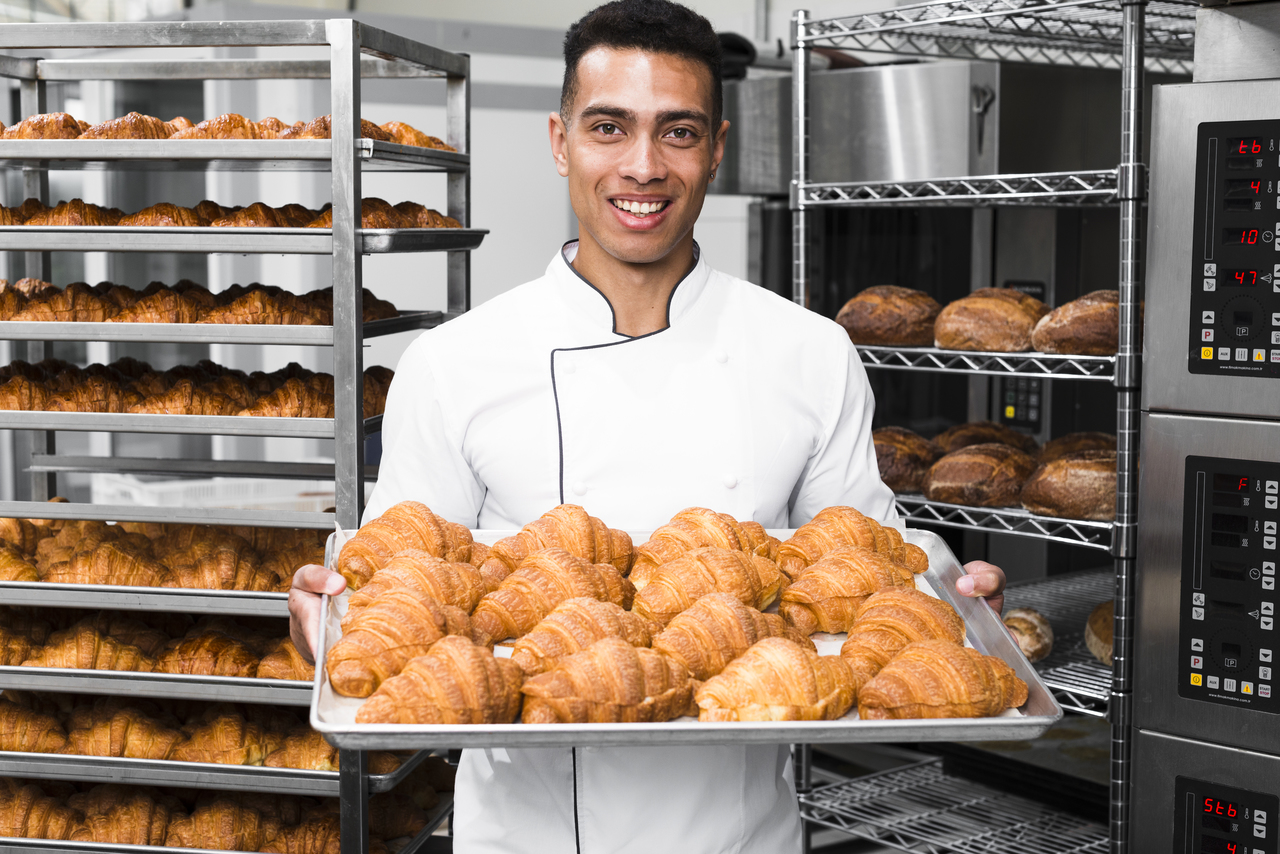 A baker holding up bread from the oven