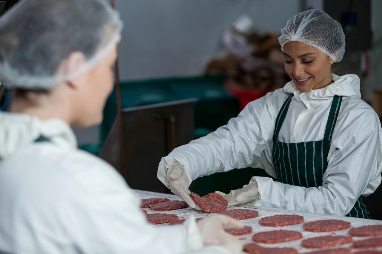 Butchers handling raw beef patties