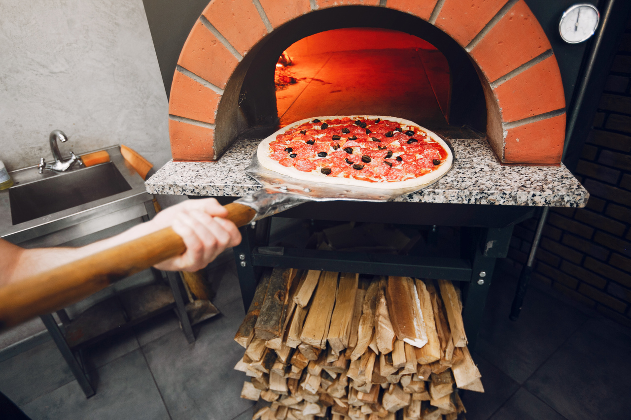 A person putting pizza into a wood fire oven